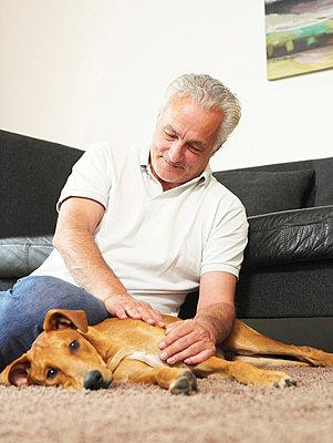 Älterer Mann streichelt Hund  - p6430064 von senior images