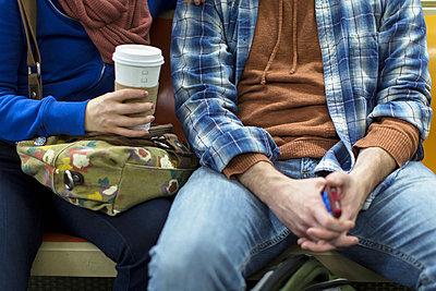 Couple sitting on urban subway - p924m768427f by Steve Prezant