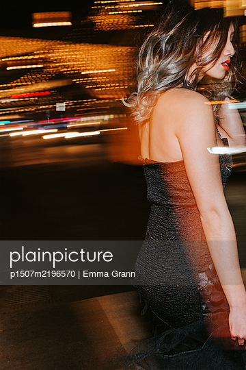 Young woman in party dress in the city at night - p1507m2196570 by Emma Grann