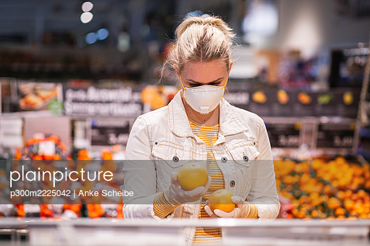 Teenage girl wearing protectice mask and gloves choosing fruits at supermarket - p300m2225042 by Anke Scheibe