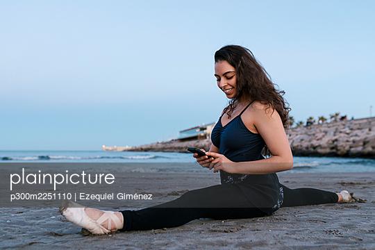 Flexible female dancer using mobile phone while doing splits at beach against clear sky - p300m2251110 by Ezequiel Giménez