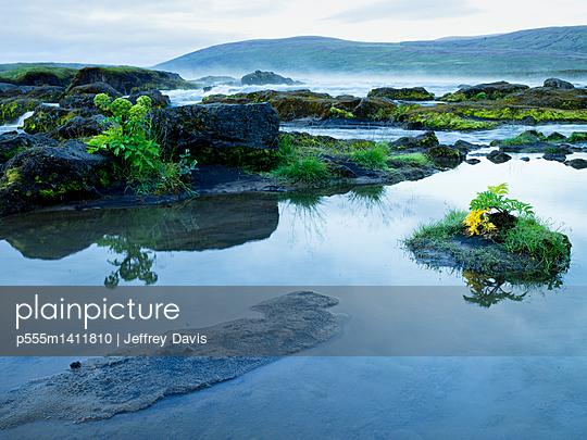 High angle view of still pond near remote waterfall - p555m1411810 by Jeffrey Davis