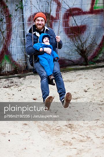 Vater schaukelt mit seinem Sohn - p795m2192235 von JanJasperKlein