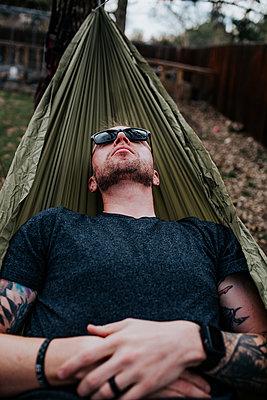 Vertical of man relaxing in hammock outside - p1166m2201330 by Cavan Images