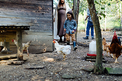 Family in a chicken pen on an organic farm - p300m2140718 by Sofie Delauw