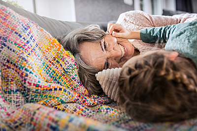 Girl and senior woman smiling while lying on sofa at home - p300m2287235 by Stefanie Aumiller