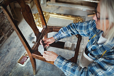 High angle view of craftsperson making wooden chair at workshop - p426m1543014 by Maskot