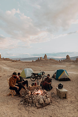 Motorcyclist road trippers around camp fire, Trona Pinnacles, California, US - p924m2068336 by Peter Amend