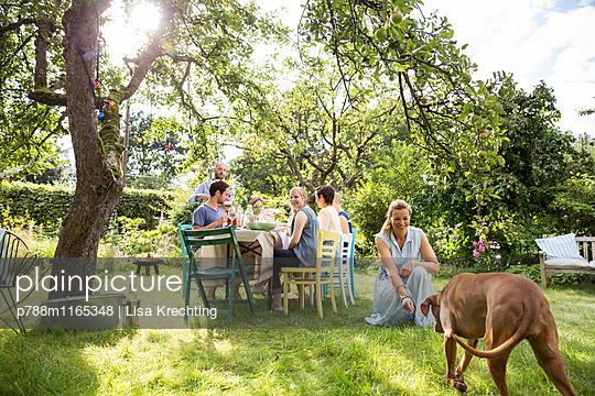 Freunde und ein Hund auf einer Gartenparty - p788m1165348 von Lisa Krechting