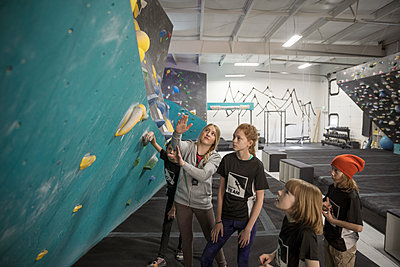 Female instructor teaching girl rock climbing students at climbing wall in climbing gym - p1192m1560059 by Hero Images