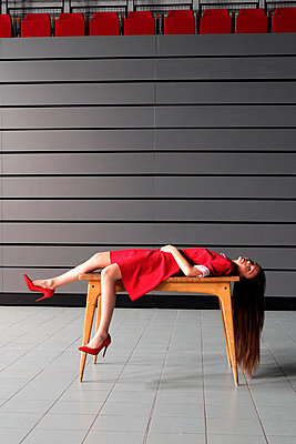 Woman in red dress lying on table - p1521m2081617 by Charlotte Zobel