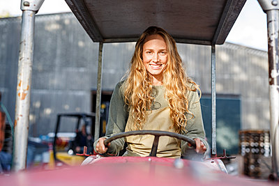 Portrait of smiling woman driving a tractor - p300m1562320 by Peter Scholl