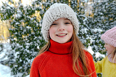 Smiling girl in knit hat standing against trees during snow - p300m2267061 by Oxana Guryanova