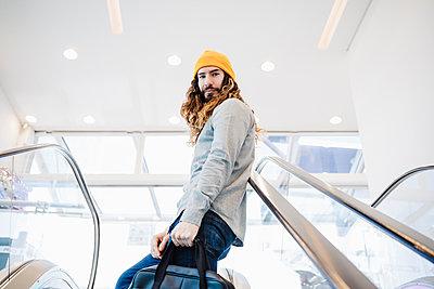 Mid adult man moving on escalator - p300m2274066 by Eva Blanco