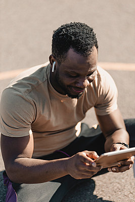African man using digital tablet while listening music through wireless headphones - p300m2275234 by Gustafsson