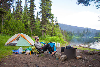 A woman relaxes at a lakeside campsite in Bowron Lake Provincial Park - p343m1101592f by Christopher Kimmel