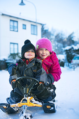Sweden, Uppland, Racksta, Brother (2-3) and sister (6-7) sitting on sled - p352m1126266f by Andreas Bylund