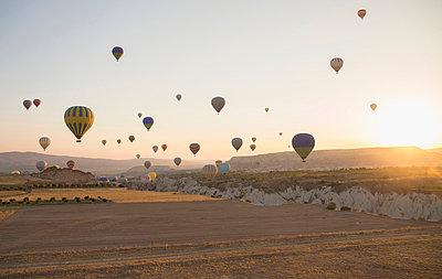 Hot air balloons above field landscape, Cappadocia, Anatolia,Turkey - p429m1022620 by Guido Cavallini