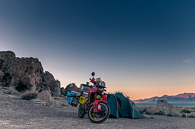 Touring bike parked by tent, Pyramid Lake, Nevada, USA - p429m2019167 by Alex Eggermont