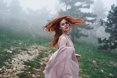 Caucasian woman tossing hair in field - p555m1504211 by Dmitry Ageev