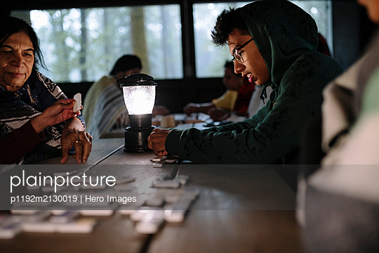 Indian family playing dominoes in log cabin by lamp light - p1192m2130019 by Hero Images