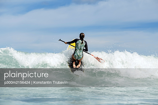 Rear view of female SUP surfer, Bali, Indonesia - p300m2156424 by Konstantin Trubavin