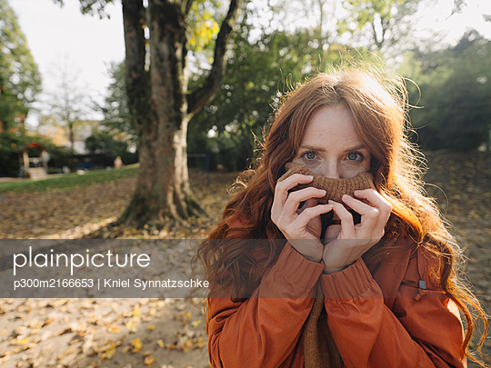 Portrait of a redheaded woman in a park in autumn - p300m2166653 by Kniel Synnatzschke