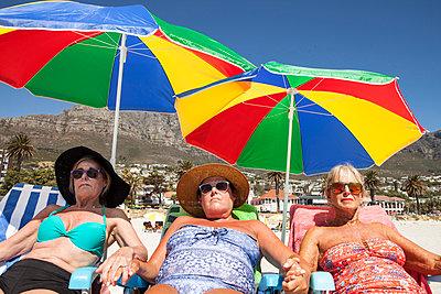 Drei coole Ladies unter bunten Sonnenschirmen - p045m1423847 von Jasmin Sander