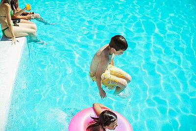 Boy and girl jumping into swimming pool - p1023m976797f by Paul Bradbury