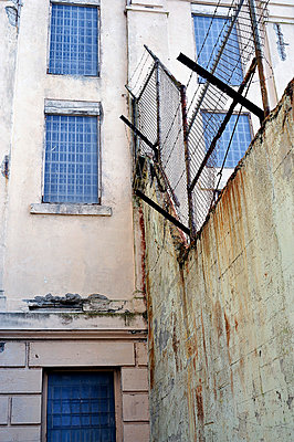 Prison wall with barbed wire - p1047m789465 by Sally Mundy