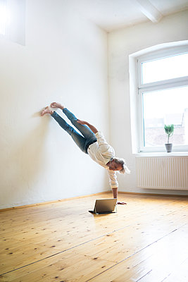 Mature man doing a handstand on floor in empty room looking at tablet - p300m1563214 by Robijn Page