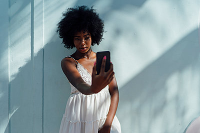 Young woman wearing white dress taking a selfie at a wall - p300m2058621 von Boy photography