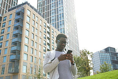 Male professional using mobile phone while standing against office building in downtown - p300m2241561 by Pete Muller