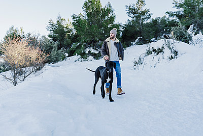 Young man and dog hiking on snow during winter - p300m2250963 by Eva Blanco