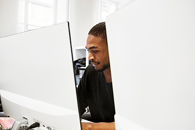 Mid adult man using computer in office - p352m2121405 by Folio Images