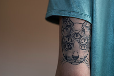 Young woman wit cat tattoo on her upper arm - p552m1362055 by Leander Hopf