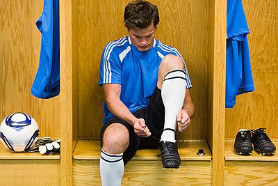 Young soccer player tying shoe - p62321772f by Sandro Di Carlo Darsa