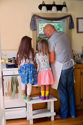 Rear view of girl and sister on stool watching father preparing food in kitchen - p924m1557837 by Kinzie Riehm