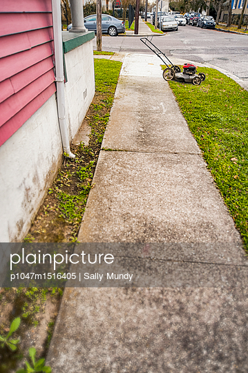 Empty street with lawnmower and parked cars - p1047m1516405 by Sally Mundy