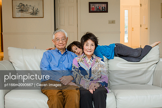 portrait Multi Ethnic Asian grandparents and grandson on couch at home - p1166m2090667 by Cavan Images