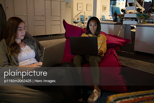 Businesswomen using laptops, working late in office lounge - p1192m2062425 by Hero Images