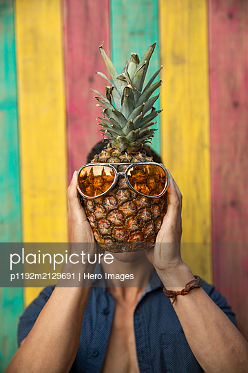 Portrait humorous young man holding pineapple with sunglasses over face on summer patio - p1192m2129691 by Hero Images