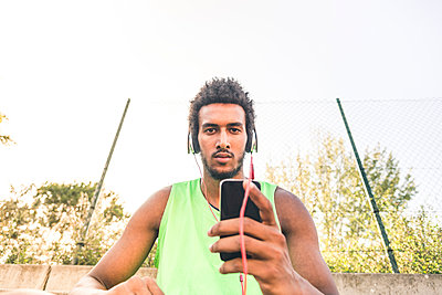 Basketball player listening music, smartphone and headphones - p300m1580754 by Francesco Morandini