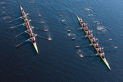 Elevated view of two rowing eights in water - p300m975564f by zerocreatives