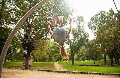 Girl swinging on playground equipment - p429m2019385 by Seb Oliver