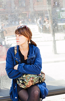 Young dark-haired woman in blue jacket sitting in a shelter and waiting for the bus   - p8476535 by Sara Arnald