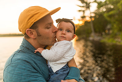 Man kissing baby daughter at lakeside - p924m1547568 by Peter Amend