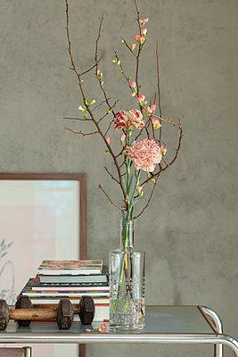Zierquitten und Nelken in alter Ginflasche vor grauer Wand mit Bücherstapel - p948m2222844 von Sibylle Pietrek