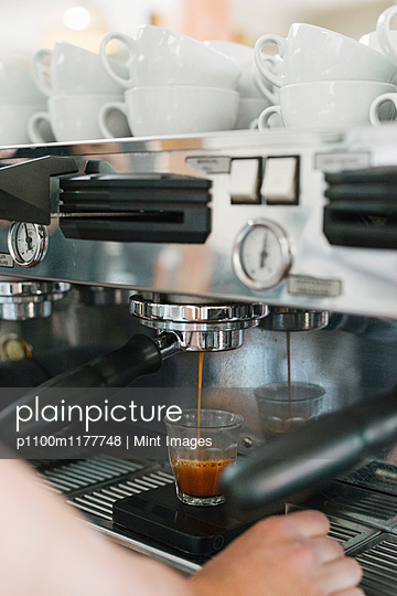 Close up of a man standing in front of an espresso machine, fresh espresso running into a cup. - p1100m1177748 by Mint Images