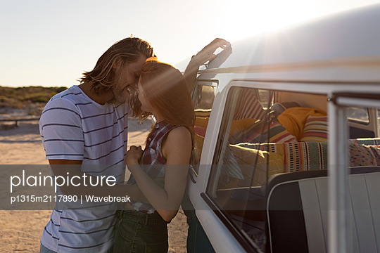 Couple kissing each other near camper van at beach - p1315m2117890 by Wavebreak